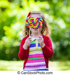 Little girl with colorful candy lollipop - Cute little girl...