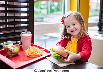 Little girl eating a hamburger in fast food restaurant -...