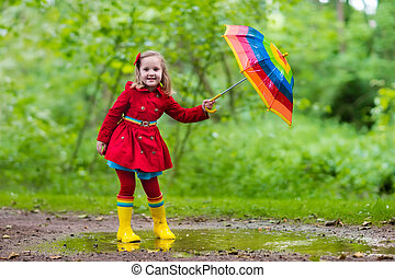 Child playing in the rain - Little girl playing in rainy...