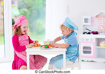 Kids playing with toy kitchen - Little girl and boy in chef...