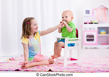 Little girl feeding baby brother - Cute little girl feeding...