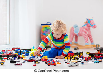 Little boy playing with toy cars - Funny curly toddler boy...
