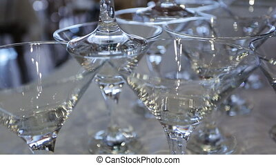 Person creates construction of crystal wine glasses on table