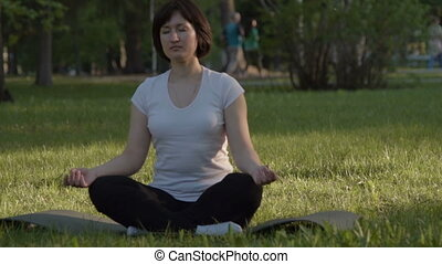 Girl in lotus pose outdoors - Young woman relaxing in lotus...