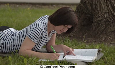 Female student studying in the park - Female student doing...