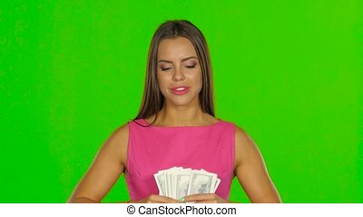 Woman is laughing and throwing money in air. Green screen....