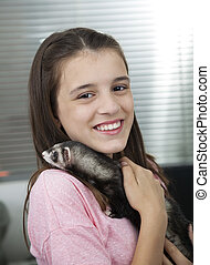 Happy Girl Holding Weasel In Veterinary - Portrait of happy...
