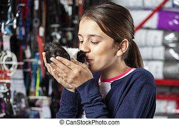 Girl Kissing Guinea Pig At Pet Store - Cute girl kissing...