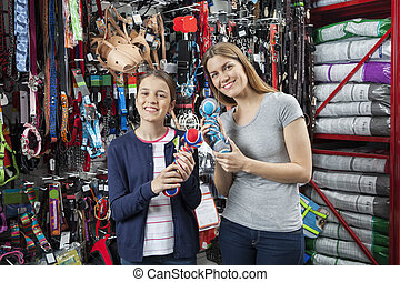 Mother And Daughter Holding Toys For Pet In Shop - Portrait...