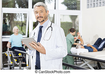 Male Physiotherapist Using Digital Tablet At Fitness Center...