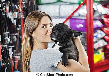 Portrait Of Woman Kissing French Bulldog At Store - Portrait...