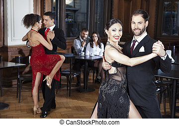 Mid Adult Man And Woman Performing Tango In Restaurant -...