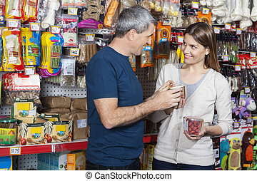 Couple Buying Pet Food In Store - Smiling couple buying pet...