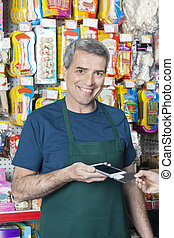 Smiling Salesman Accepting Credit Card Payment From Customer
