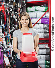 Female Customer Holding Pet Food Bowl At Store - Portrait of...