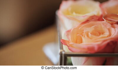 Composition of orange roses stands on table with bridal rings on it.