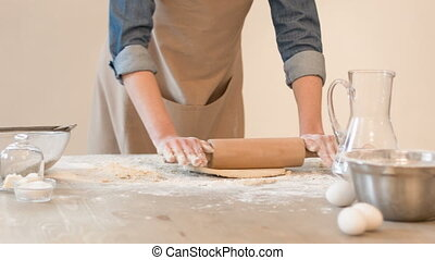 Pleasant concentrated woman rolling dough