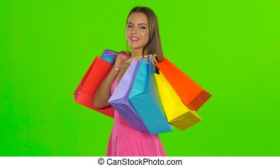 Woman smiling while holding shopping bags. Green screen