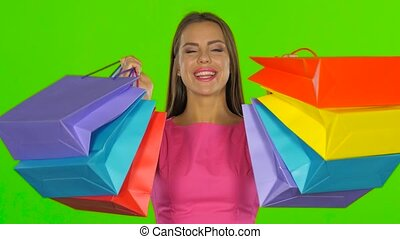 Woman joyfully looks out from behind shopping bags. Green...