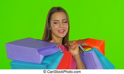 Woman holding shopping bags and smiling Green screen Close...