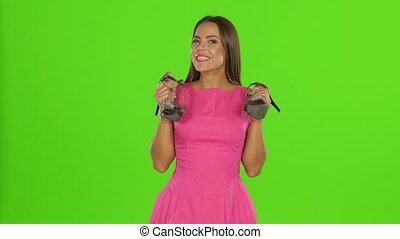 Woman chooses shoes. Green screen - Smiling girl holding...