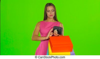 Woman looking at purse and dissatisfied. Green screen