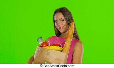 Woman holding bag with groceries food. Green screen. Close up
