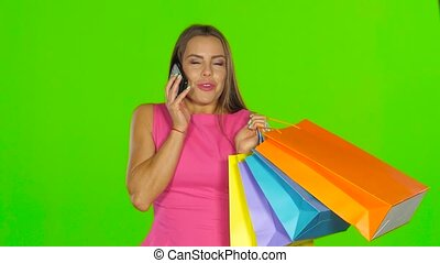 Woman with shopping bags talking on the phone Green screen...