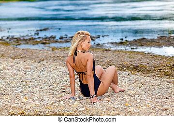 girl in a black bikini swimsuit on the stony beach. Sexy...