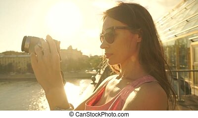 Beautiful brunette girl in pink dress with camera standing on the bridge. Slow motion steadicam clip