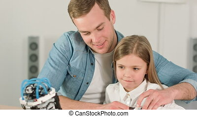 Loving father and his daughter playing with robot toy -...