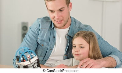Cheerful father and his daughter playing with robot toy -...