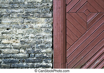 Old brick wall with wooden door fragment. Texture background. Close up.