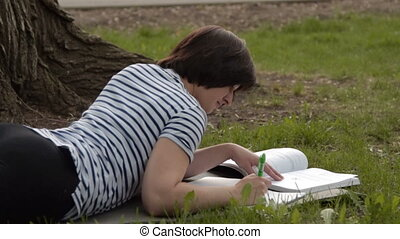 Girl student taking notes outdoors - Girl student lying on...