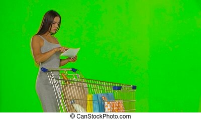 Woman checks the shopping list. Green screen - Beautiful...