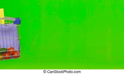 Woman wheeling a cart with food. Green screen. Close up