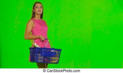 Woman with shopping basket choosing products. Green screen