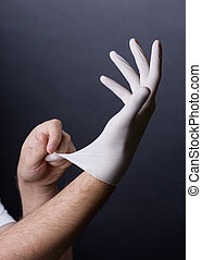 Putting on latex gloves - Male hands in golves. Doctor or...