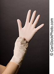 Putting on latex gloves - Female hands in golves. Doctor or...