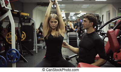 Woman shakes her triceps with dumbbells with coaching. She...