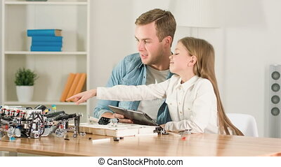 Cheerful father and daughter constructing robot toy - Our...