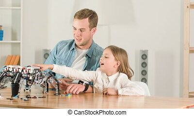 Positive father and his daughter sitting at the table