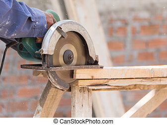 Carpenter using circular saw in loggers - Carpenter using...