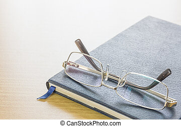 Glasses put on text book - Glasses put on a text book on...