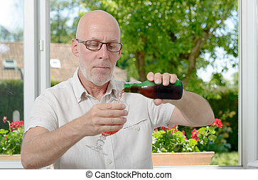 middle-aged man drinking a glass of beer