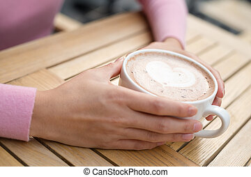 Woman having coffee at outdoor cafe
