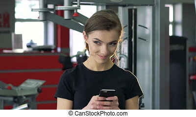 Close-up of a girl with a phone in the gym