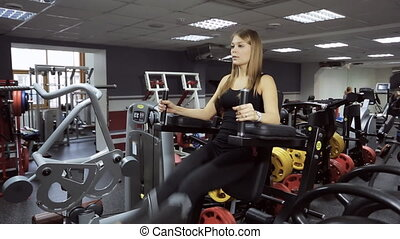 A woman performs an exercise on pumping up press on...