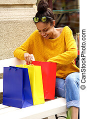Happy young woman looking into shopping bags