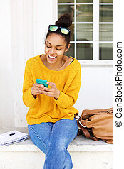 Cheerful young woman sitting outside using cellphone -...